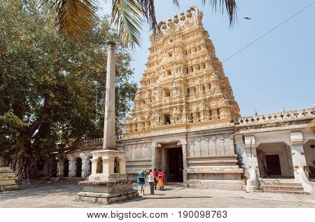 BANGALORE, INDIA - FEB 17, 2017: People walking around beautiful Hindu temple with carved gopuram gates on February 17, 2017. With population 8.52 million Bangalore is the third most populous indian city