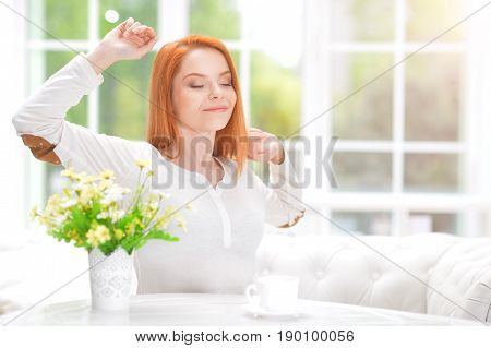 Beautiful young woman stretching oneself while sitting at table