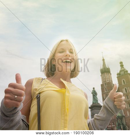 Female tourist in a yellow dress stands on a background of the church of St. Mary in Krakow. Basilica Mariacka. Krakow. Poland.