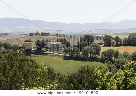 VAL D'ORCIA. ITALY - JUNE 3 2017: Hills surrounding Val D'orcia area in Tuscany region of Italy with houses and cypress in the background
