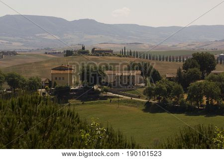 VAL D'ORCIA, ITALY - JUNE 3 2017: Hills surrounding Val D'orcia area in Tuscany region of Italy with houses and cypress in the background