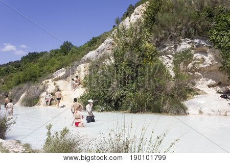 BAGNO VIGNONI, ITALY - JUNE 3 2017: People bathing in the free area of Bagno Vignoni in Tuscany Italy free accessible hot springs puddle trough vegetation