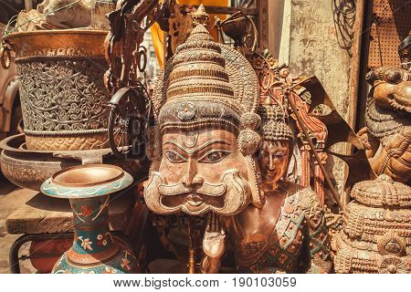 BANGALORE, INDIA - FEB 14, 2017: Wooden mask of Indian man with a mustache and vintage artworks of antique store on February 14, 2017. With populat. 8.52 million Bangalore is 3rd most populous indian city