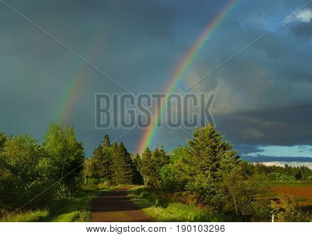 A rainbow over the Trans Canada Trail or the Confederation trail in rural Prince Edward Island, Canada.