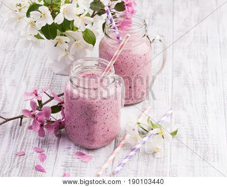 Berry Smoothie Or Milkshake In Jar On White Wooden Rustic Background