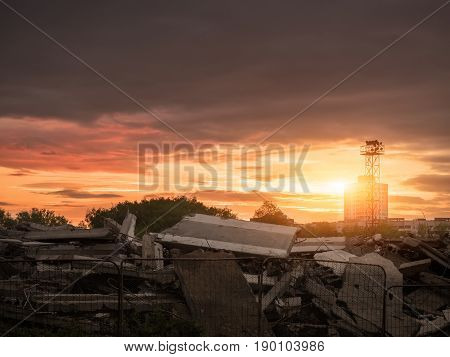 Destroyed building against the backdrop of the city and the sunset. Demolition of old buildings. Preparation for construction.