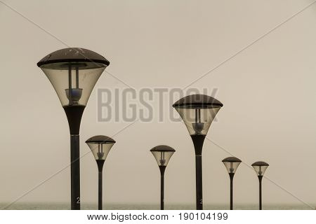 Arrangement of streetlamps against a cloudy sky