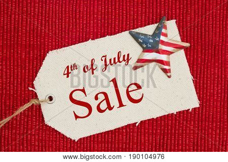 4th of July Sale text on a cloth gift tag with a retro American flag star on shiny red material
