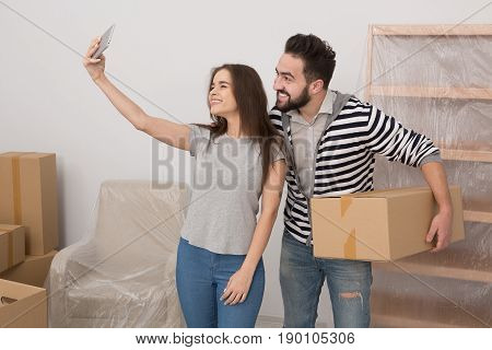 Couple making selfie in new apartment leaving old life behind. Man and woman standing in new apartment in the room full of new furniture, man holding box and woman holding phone.