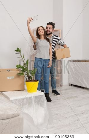Man and woman in casual clothes standing in new home after relocation, forwarding to new life. Couple making selfie shot in living room witn new furniture.