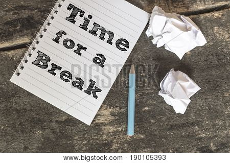 Time for a Break on a notebook with pen crumpled paper on wooden table.
