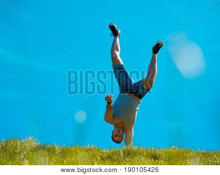 The guy is standing on one hand. Background blue sky. Below the green grass.
