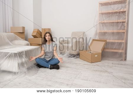 Young female sitting in relaxation pose on the floor after relocation to new home. Girl sitting on the floor with lots of unpacked boxes behind her.