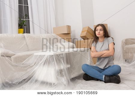 Brunette young woman trying to be patient while relocating to new apartment. Female sitting on the floor in new flat with lots of unpacked boxes in the room with furniture covered with foil.