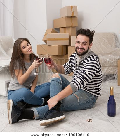 Relocation is time for joy and happiness. Couple celebrating relocation to new home. Man and woman sitting on the floor holding wineglasses.