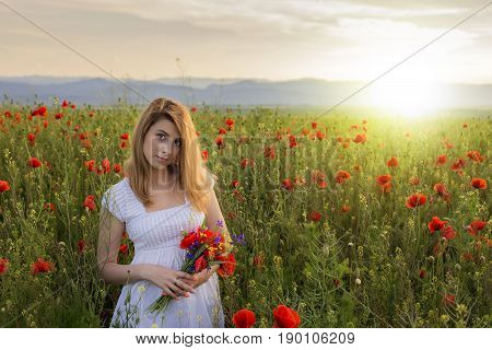 Woman in white dress holding bouquet of poppies standing on the field