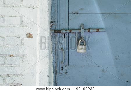 Padlock on the blue metal door. Locked on the castle is an old door in a white brick wall. Abstract background