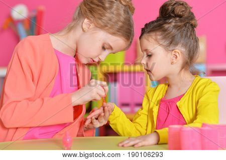 cute little girls with stylish hairstyles doing manicure
