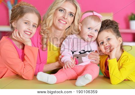 Portrait of happy mother with three adorable daughters