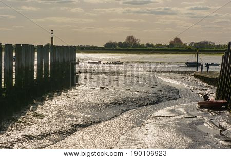Bosham Quay in Chichester Harbour West Sussex England. Low tide showing mud. High contrast photograph against the light. Unrecognizable people.