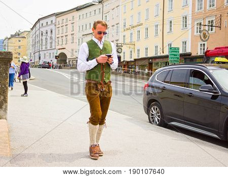 Salzburg, Austria - May 01, 2017: Men wearing traditional Austrian costume going with mobile phone at street on sunny day at Salzburg, Austria on May 01, 2017