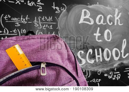 Back to school background with purple school bag with yellow ruler and the title