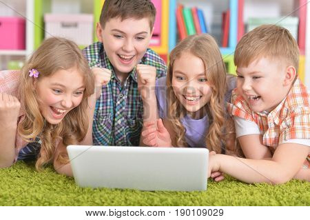 Group of children lying on floor with green carpet and looking at modern laptop