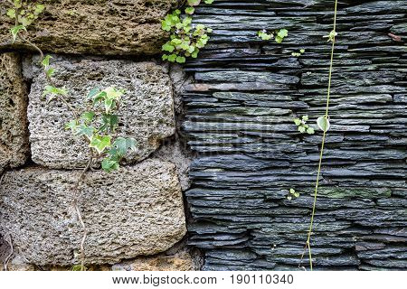 Junction of walls with two different textures. Layers of uneven black stone side by side to grungy pumice bricks. Natural background and texture for design