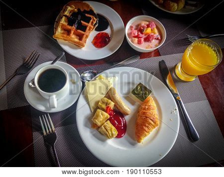 Tasty hearty Breakfast served with coffee, orange juice, cheese, fruit yogurt and waffles