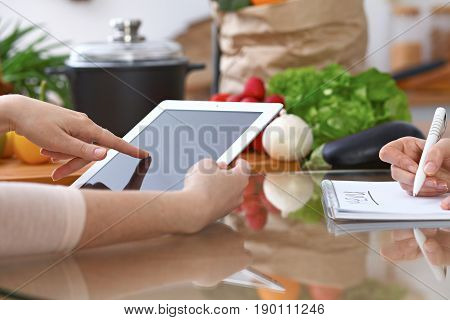 Human hands of two female persons using touchpad for making menu in the kitchen. Closeup of two women are making online shopping by tablet computer and credit card. Cooking and shopping concept