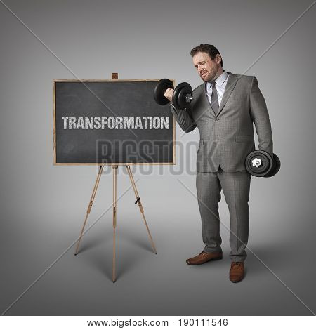 Transformation text on blackboard with businessman holding weights