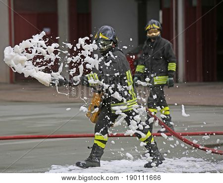 Firefighters While Extinguishing The Fire With Foam