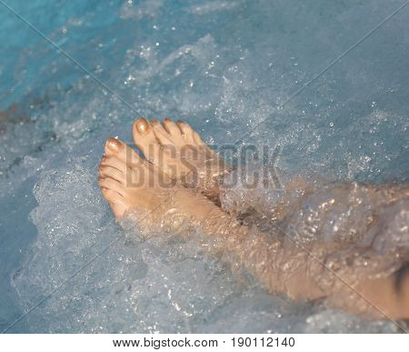 Woman In Spa Pool And Whirlpool At Her Feet With Nails With Enam