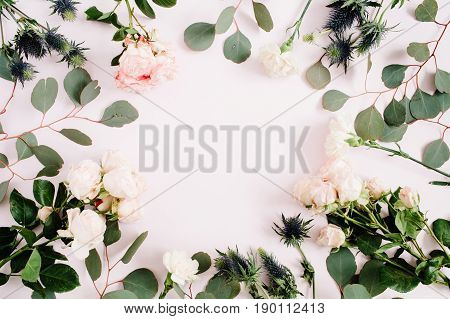 Round frame wreath made of beige rose flowers eringium flower eucalyptus branches and leaves on pale pastel pink background. Flat lay top view. Floral background