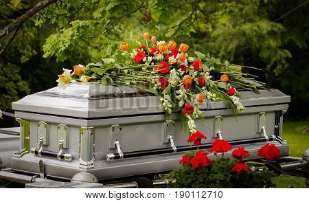 Silver casket covered in beautiful orange and red flowers.