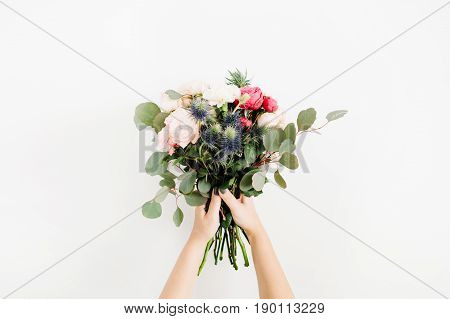 Beautiful flowers bouquet in girls hands: bombastic roses blue eringium eucalyptus isolated on white background. Flat lay top view. Floral composition