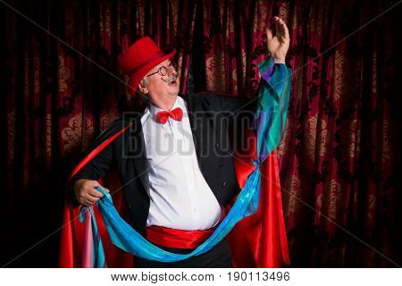 Funny senior magician performer doing magic tricks on stage