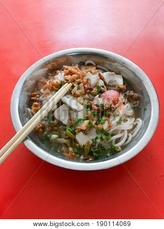 Dish With Udon Noodles Soup On Red Table