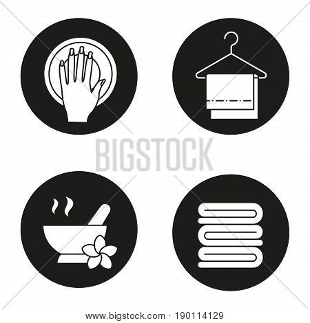 Spa salon icons set. Hand with manicure, mortar and pestle, clean spa salon towels on clothes hanger. Vector white silhouettes illustrations in black circles