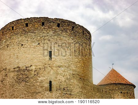 Walls arched windows and the pointed conical roof of Fortress Akkerman in the morning mist, Bilhorod-Dnistrovskyi, Ukraine. This medieval fortress dates from the 13th century.