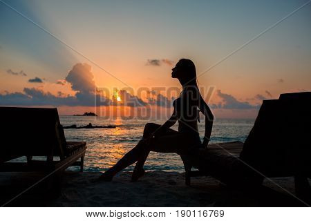 Silhouette of a beautiful slender girl on a sunset background and sun loungers on the ocean shore. Woman watch skyline sunrise on near deck chair at the sea beach. Vacation Concept.