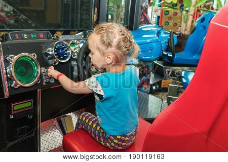 Little girl at the wheel of the game simulator presses the buttons