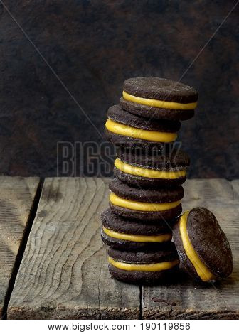 Chocolate Sandwich Cookies With Orange Cream Piled High Back On A Dark Background