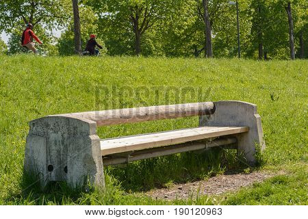 Massive wood-stone bench in a park invites to rest