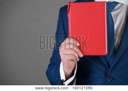 red book in hand of man or businessman in blue outfit on grey background copy space business saving book