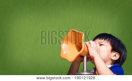 Boy yelling in to Megaphone on green board copy space
