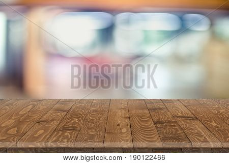 Empty wood table perspective on blurred background. Wood table perspective for design. Wood table surface. Rustic wood table perspective on blurred background. Large dinner wood table with blurred back. Wood table texture background. Wood table worktop.