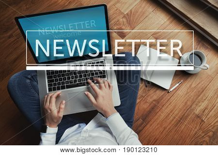Top view of young woman sitting on the wooden floor with laptop and coffee with newsletter inscription in the foreground