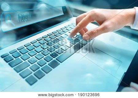 Closeup of hand using computer keyboard. Closeup of businesswoman hand using computer laptop keyboard with written in search bar on virtual screen