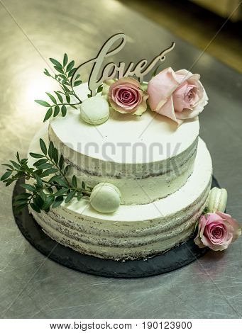 Beautiful wedding cake with cream With text Love on top and pink flowers roses